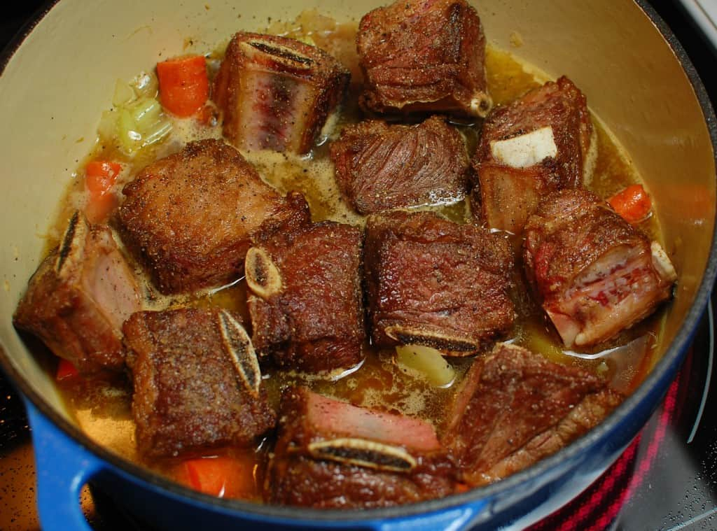 Braised beef short ribs with vegetables in a dutch oven