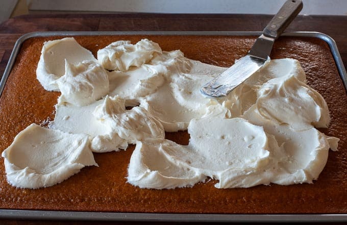 Cream cheese frosting ready to be spread in the pumpkin bars.