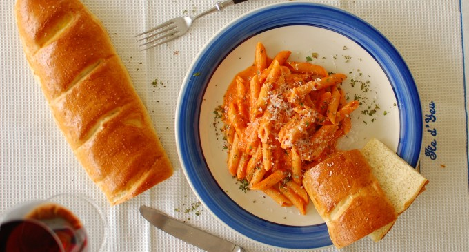 penne with vodka sauce in a bowl with home baked baguette