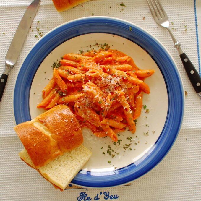 penne with vodka sauce in a blue rimmed bowl