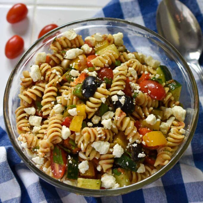 clear glass bowl of cold pasta salad on a blue checkered cloth