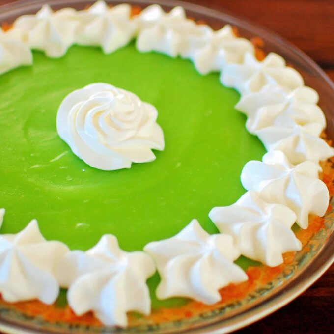 Side view of lime pie with whipped cream.