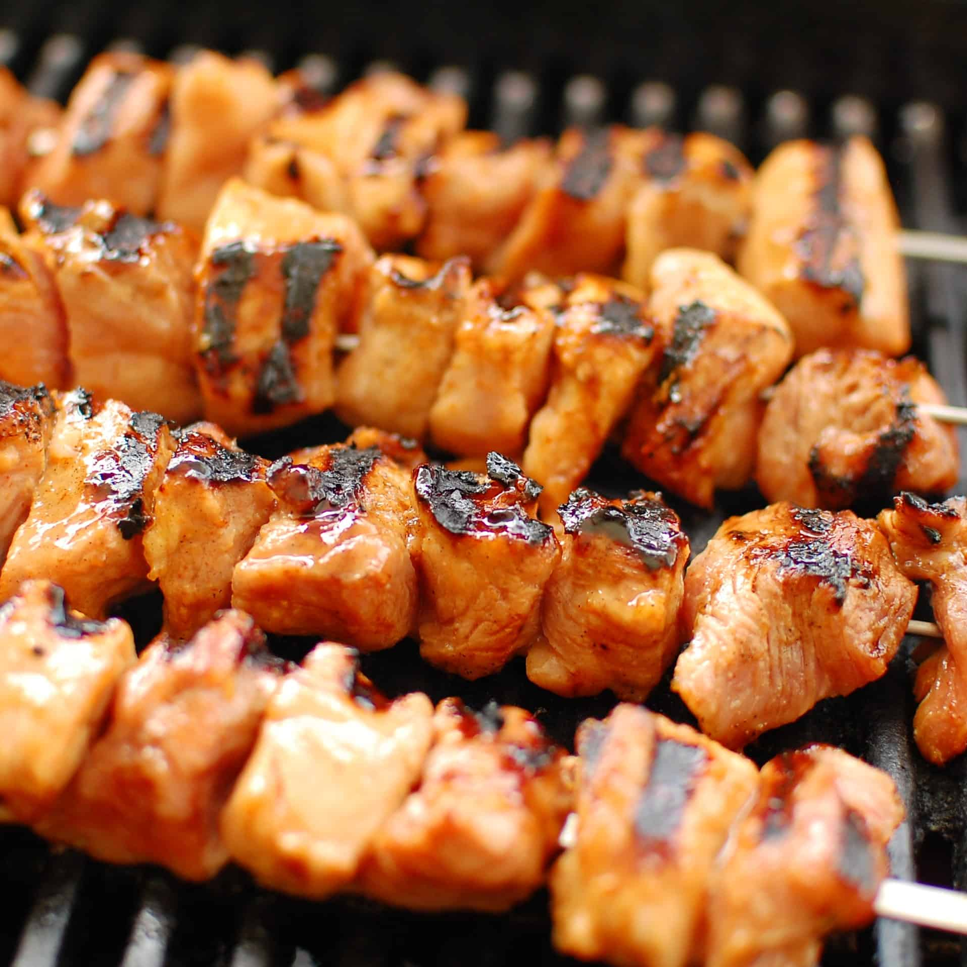 Pork on skewers on a grill.