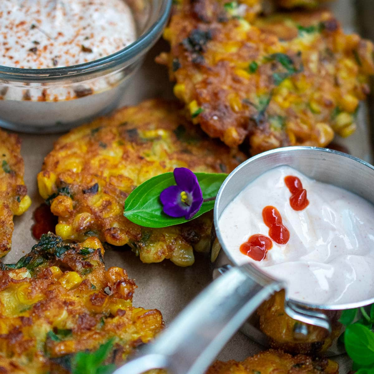 Close up view of fritters with 2 sour cream sauces.