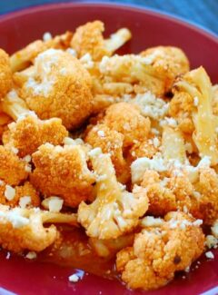 Roasted Cauliflower in Buffalo Sauce - sprinkled with crumbled blue cheese. What a delicious treat! | joeshealthymeals.com