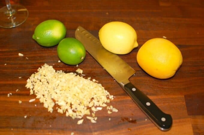 2 limes, 1 lemon and 1 orange with chopped garlic on a cutting board.