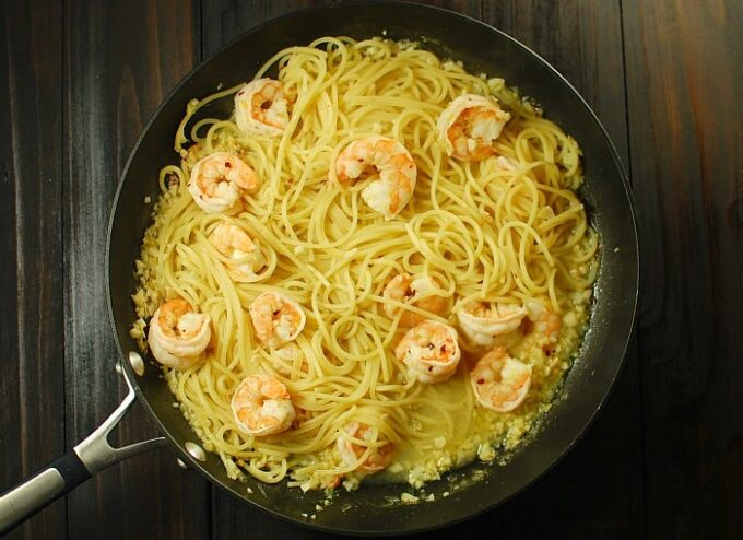 Shrimp on spaghetti in a skillet.