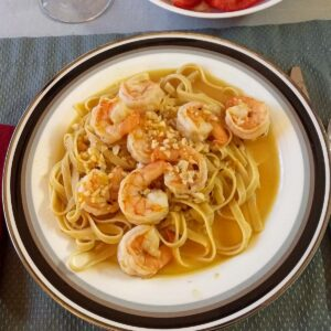 Plate of shrimp on fettuccini with wine sauce.
