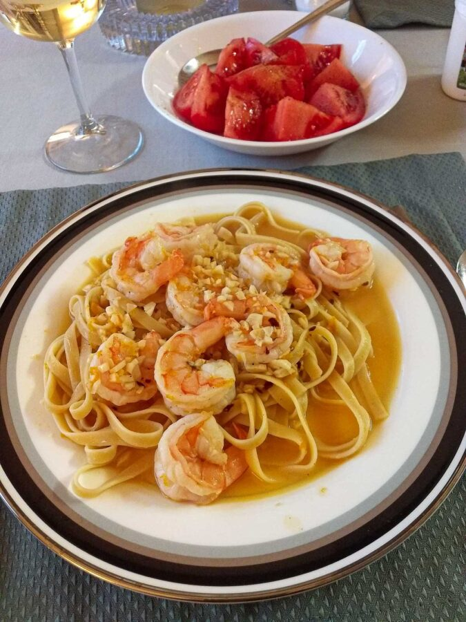 Plate full of citrus and garlic shrimp on pasta.