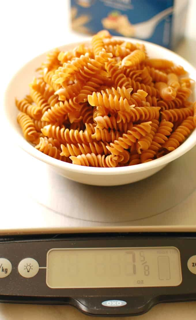 8 ounces of pasta in a bowl on a kitchen scale.