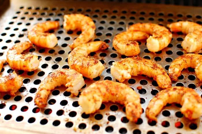 Seasoned shrimp on a gas grill.