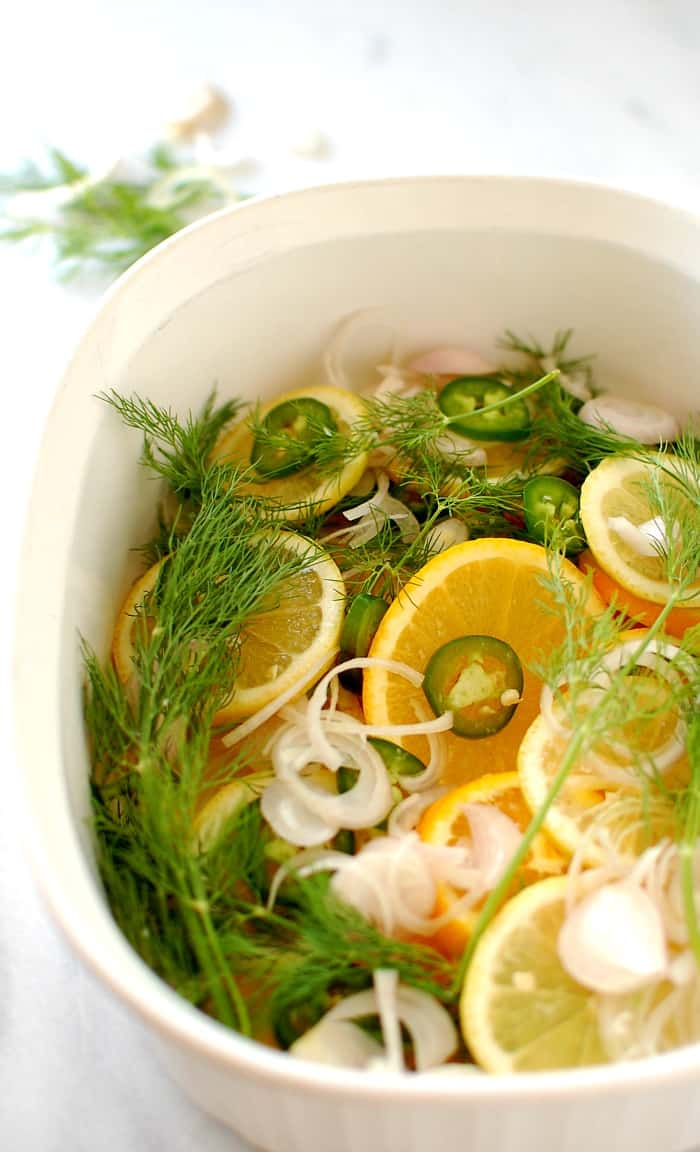 Casserole dish with citrus slices, onions and dill weed.
