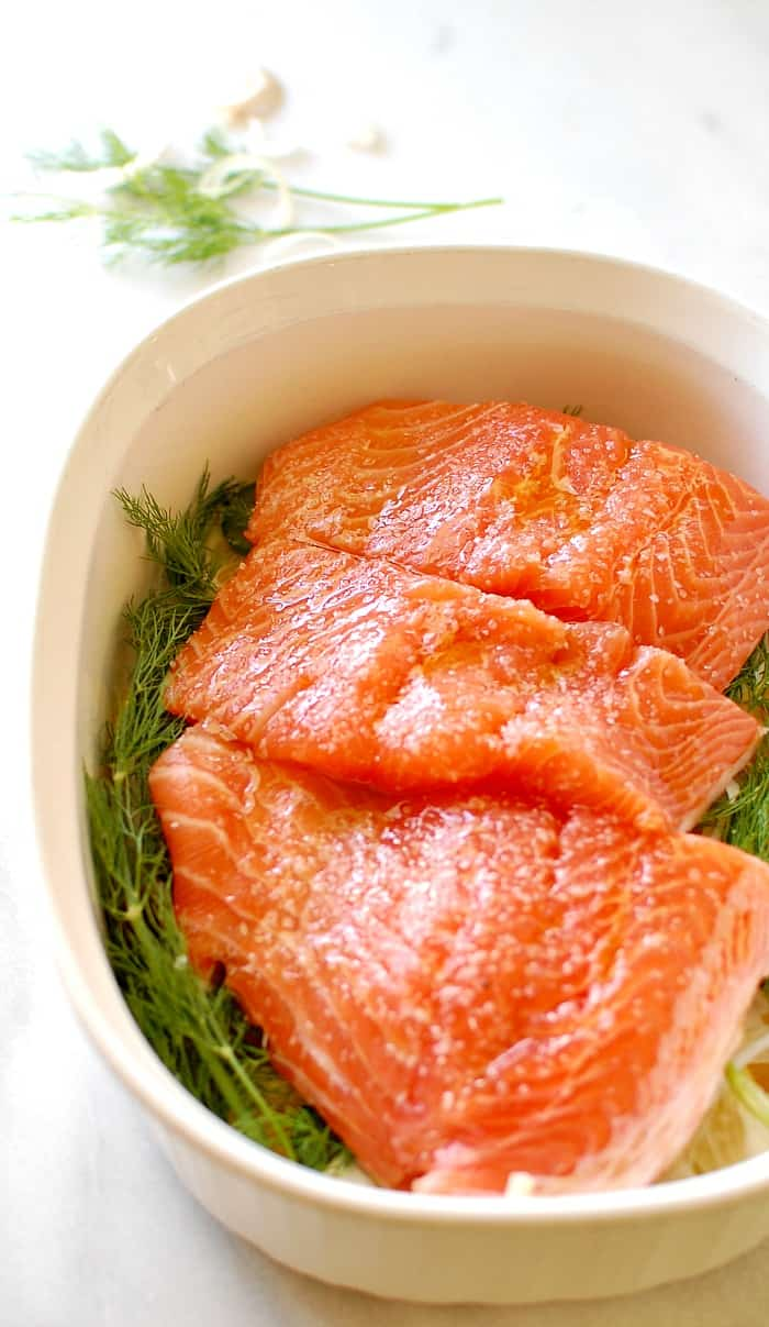 Raw salmon in a casserole dish with dill weed.