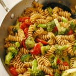 Overhead view of pasta and vegetables in a skillet.