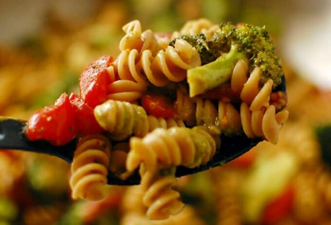 Close-up spoonful of tomato broccoli pesto pasta.