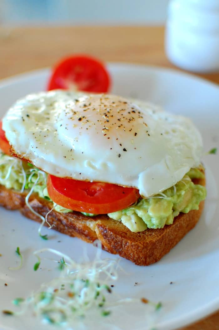 Close-up view of fried egg and tomato slice on Avocado toast.