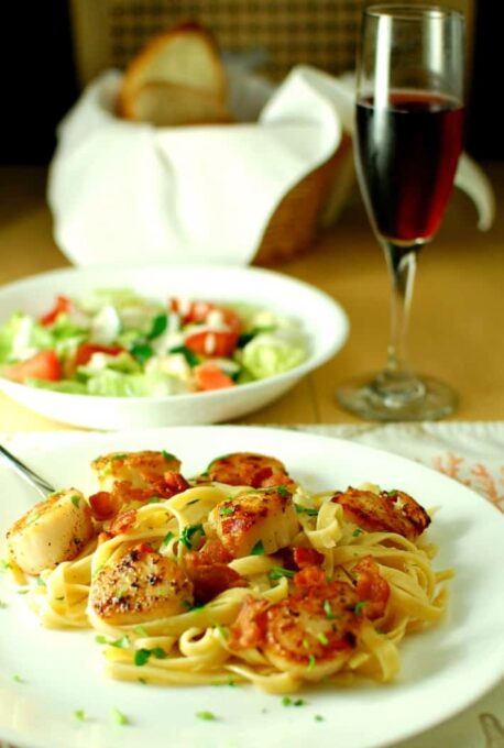 Side view of pasta with scallops.