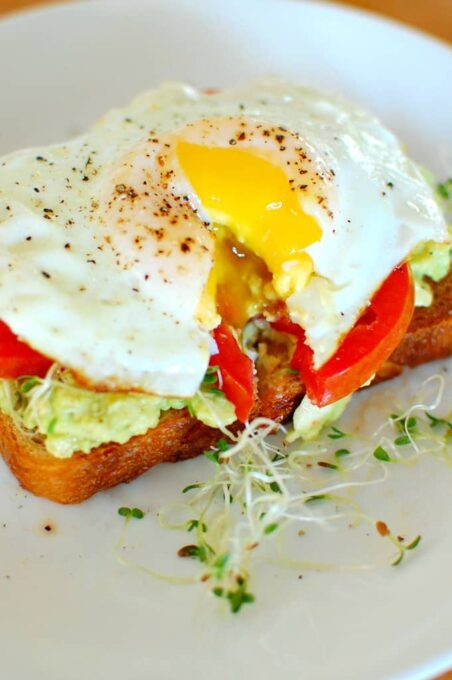 Avocado toast with egg and sprouts. Great for breakfast or brunch. | joeshealthymeals.com