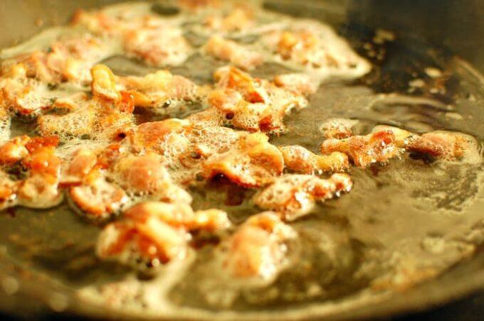 Bacon frying in carbon steel pan.