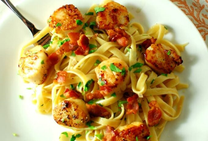 Seared scallops and pasta on a white plate.