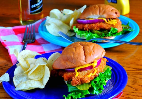 Breaded pork tenderloin sandwich on a blue plate.