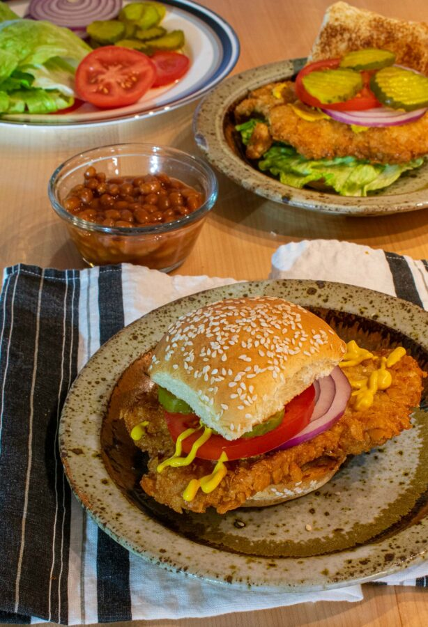 Two breaded pork sandwiches with a small bowl of baked beans.