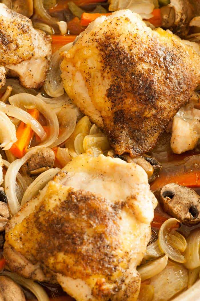 Baked chicken thighs with vegetables. Super easy recipe for a busy family and the flavor is outstanding! | joeshealthymeals.com