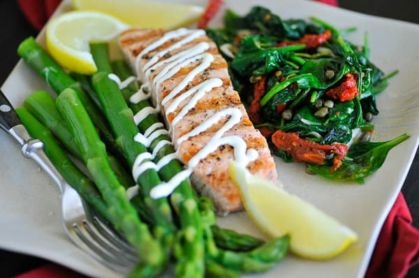 Dinner plate of salmon, asparagus, and spinach.