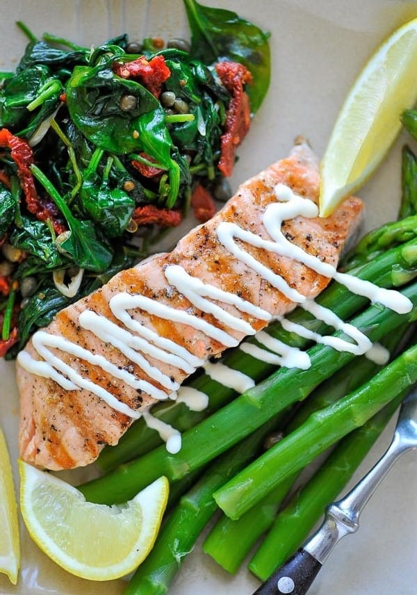Plate of wilted spinach, salmon and asparagus.
