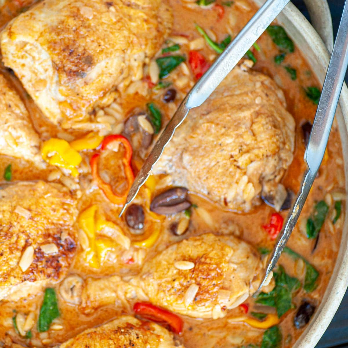 Overhead view of chicken with tongs.