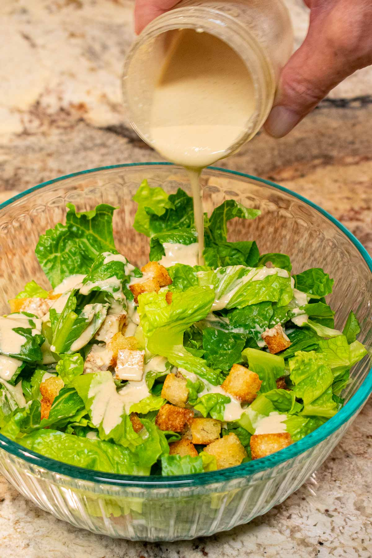 Caesar dressing being poured over romaine lettuce in a bowl.
