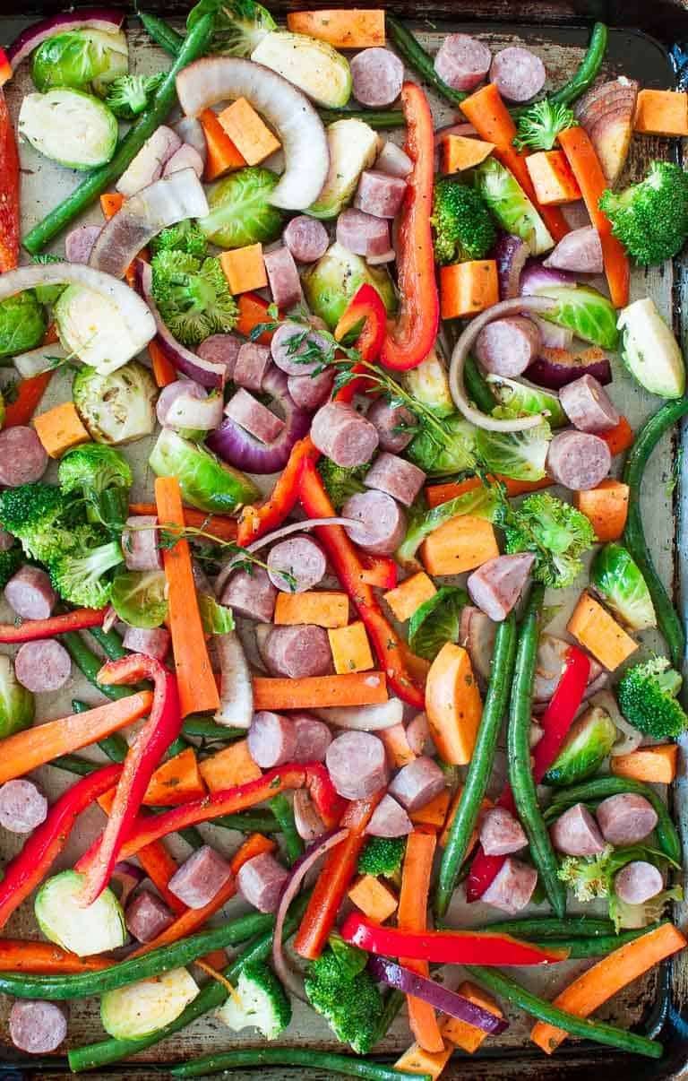 Sheet pan with raw vegetables ready for the oven.