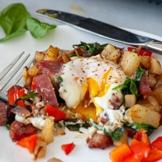 Plate of breakfast hash and fried egg.