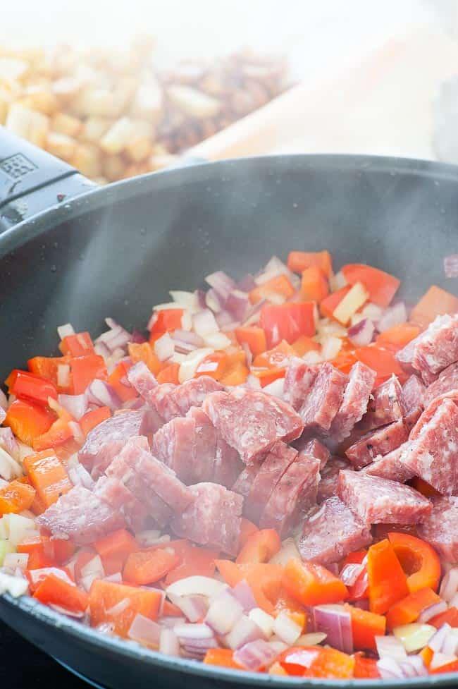 Adding salami to the breakfast hash.