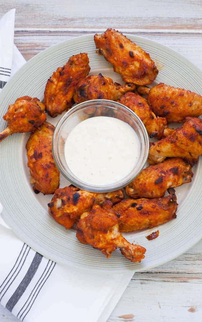 Chicken wings on a white plate with blue cheese dip.