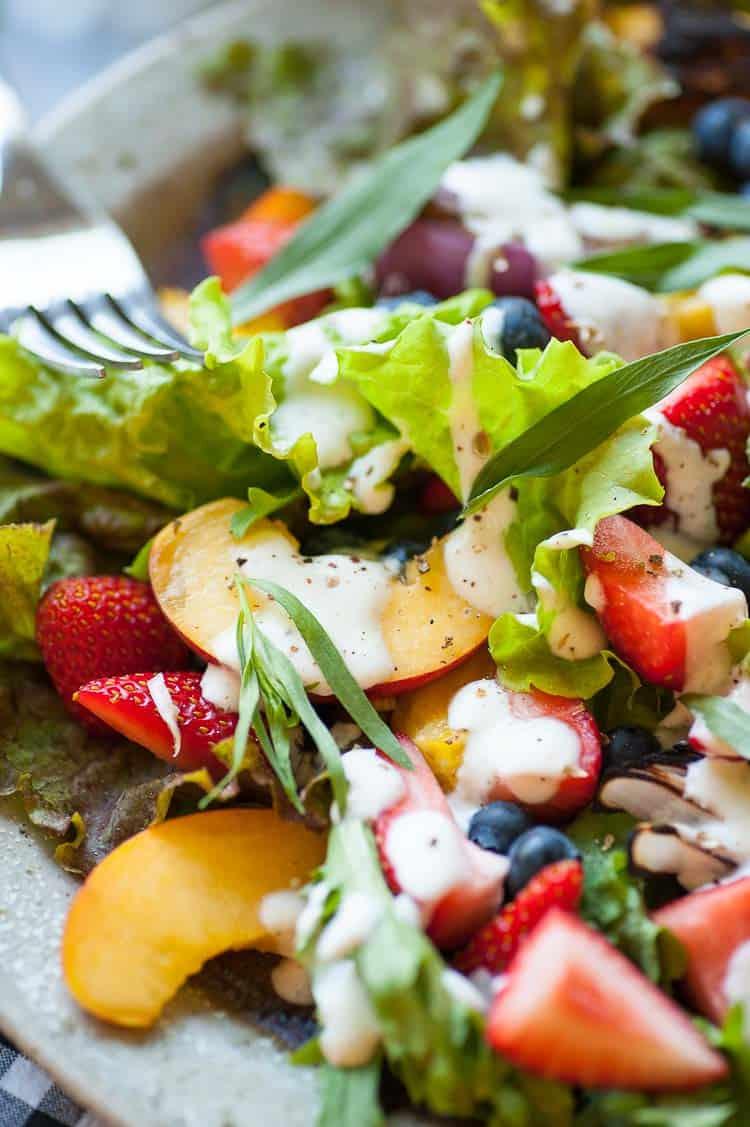 Close up garden greens salad with fruit and yogurt dressing