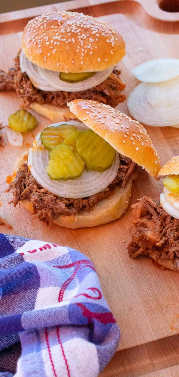 Pulled pork sandwiches with sliced onions and dill pickle chips.