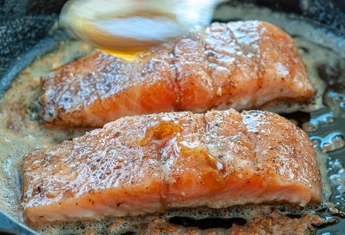 Honey being drizzled on salmon filets that are ready to place under a broiler to finish cooking.