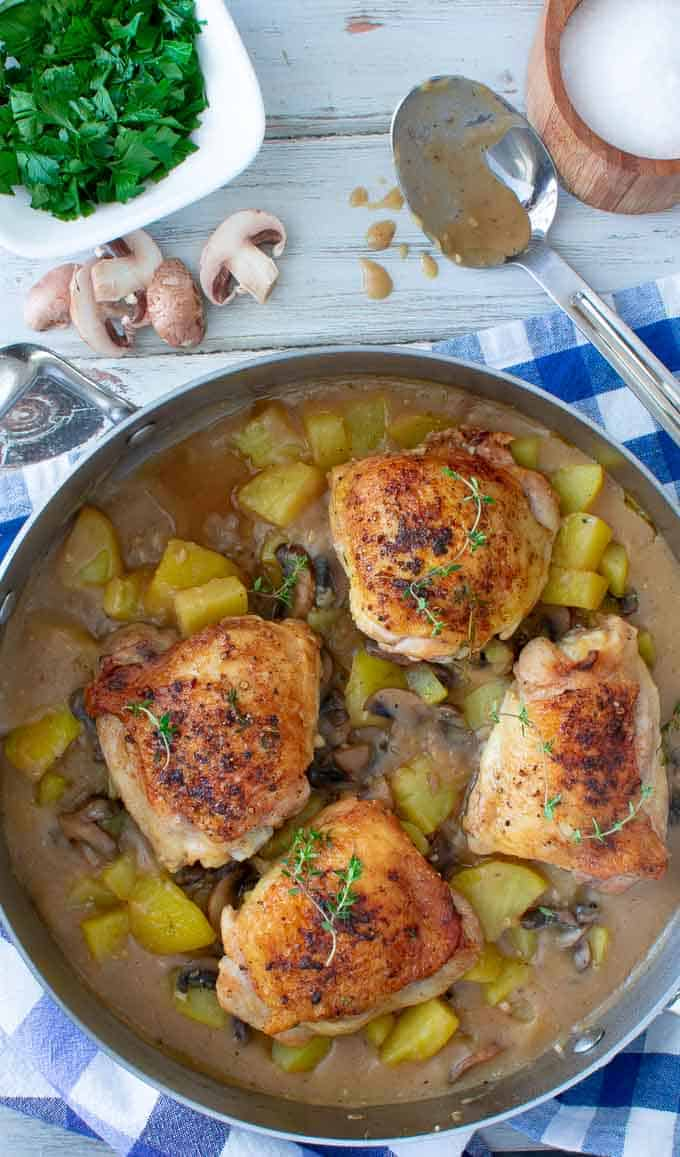 overhead view of chicken thighs with potatoes and gravy in a skillet