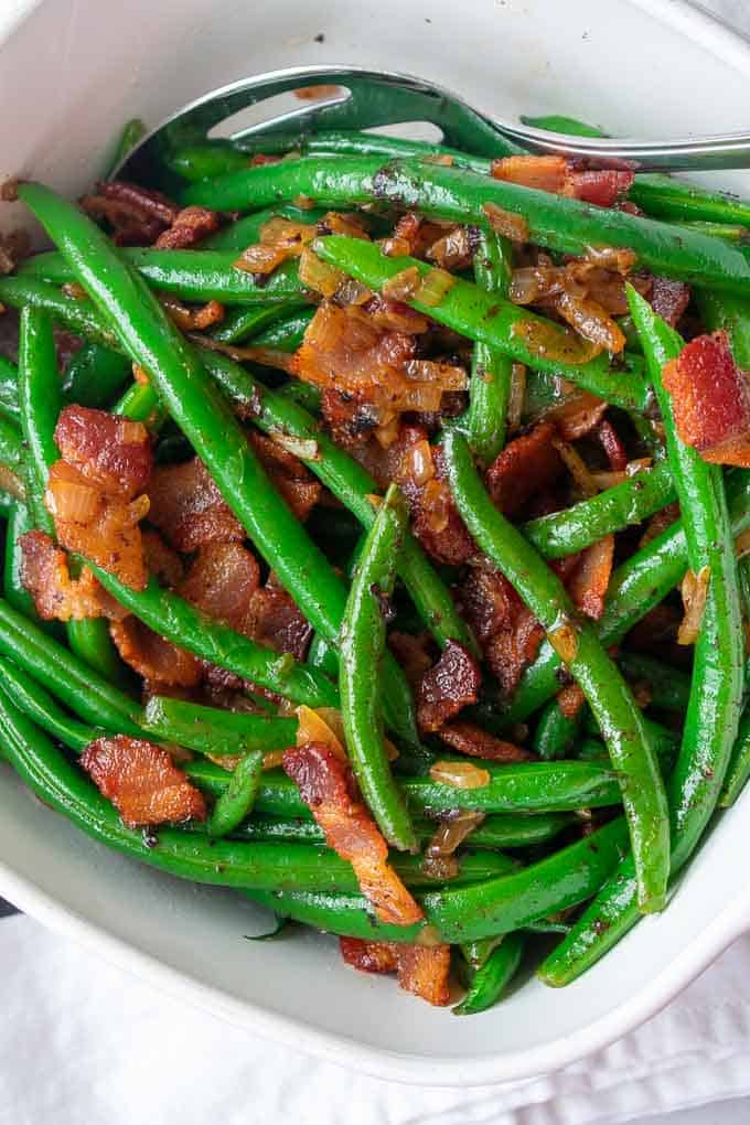 close up of green beans with bacon and onions