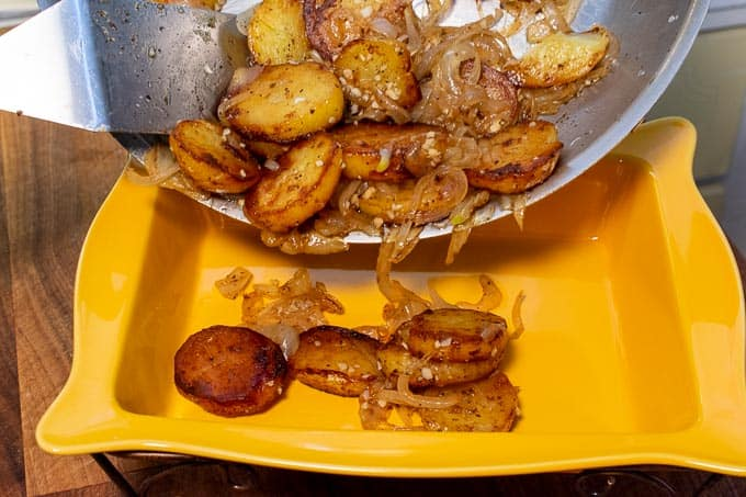 pouring fried potatoes and onions into a serving dish