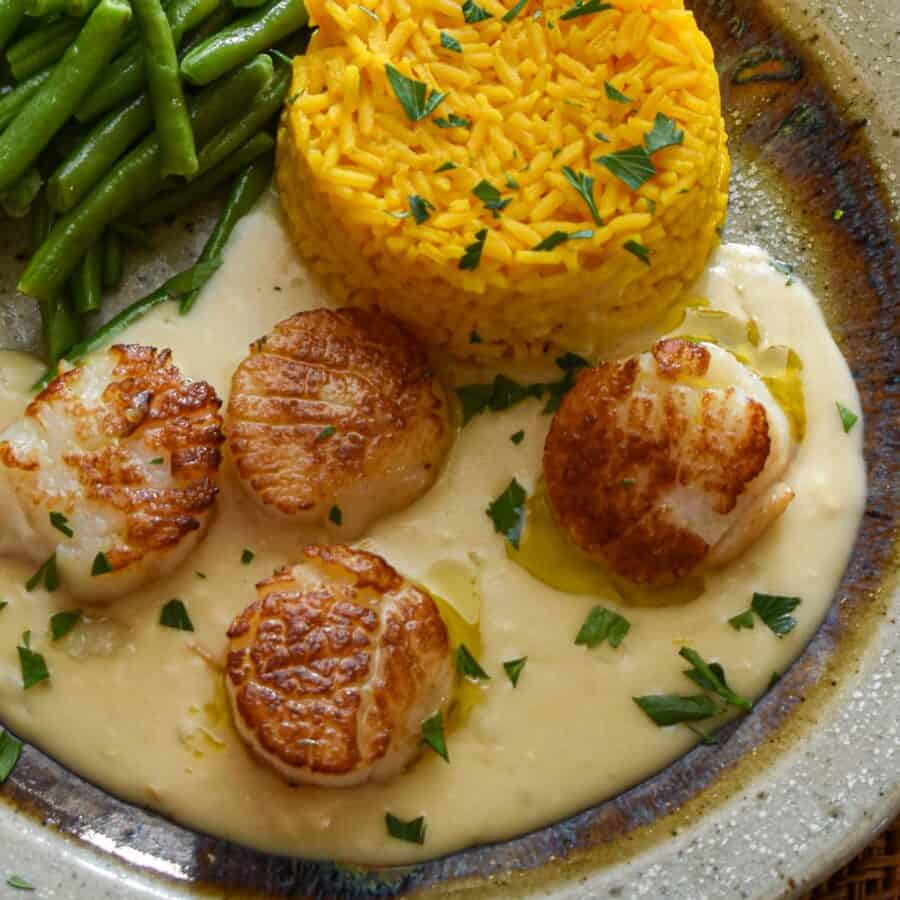 Close up view of seared scallops on lobster brandy sauce.
