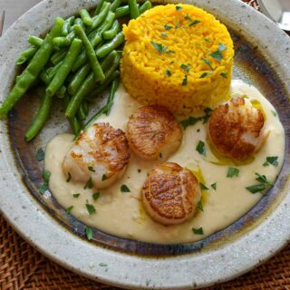 Plate of seared scallops on lobster brandy sauce.