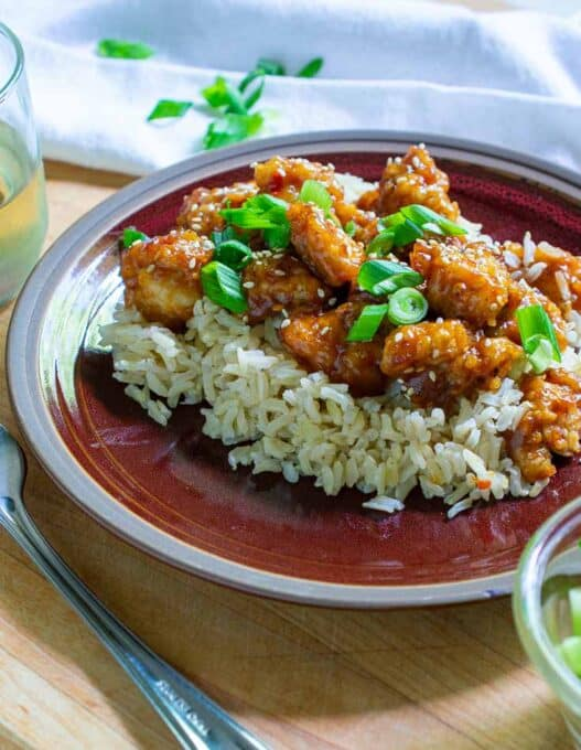 Close-up of General Tso chicken on a red plate.