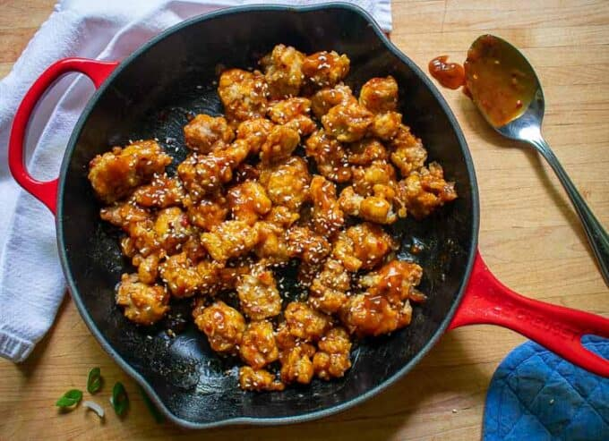 Skillet of chicken coated with sweet and sour sauce.