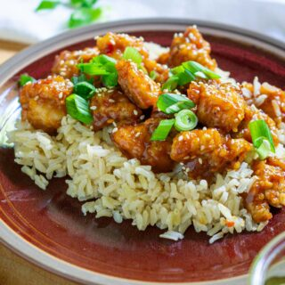 plate of General Tso chicken on a bed of rice garnished with green onion