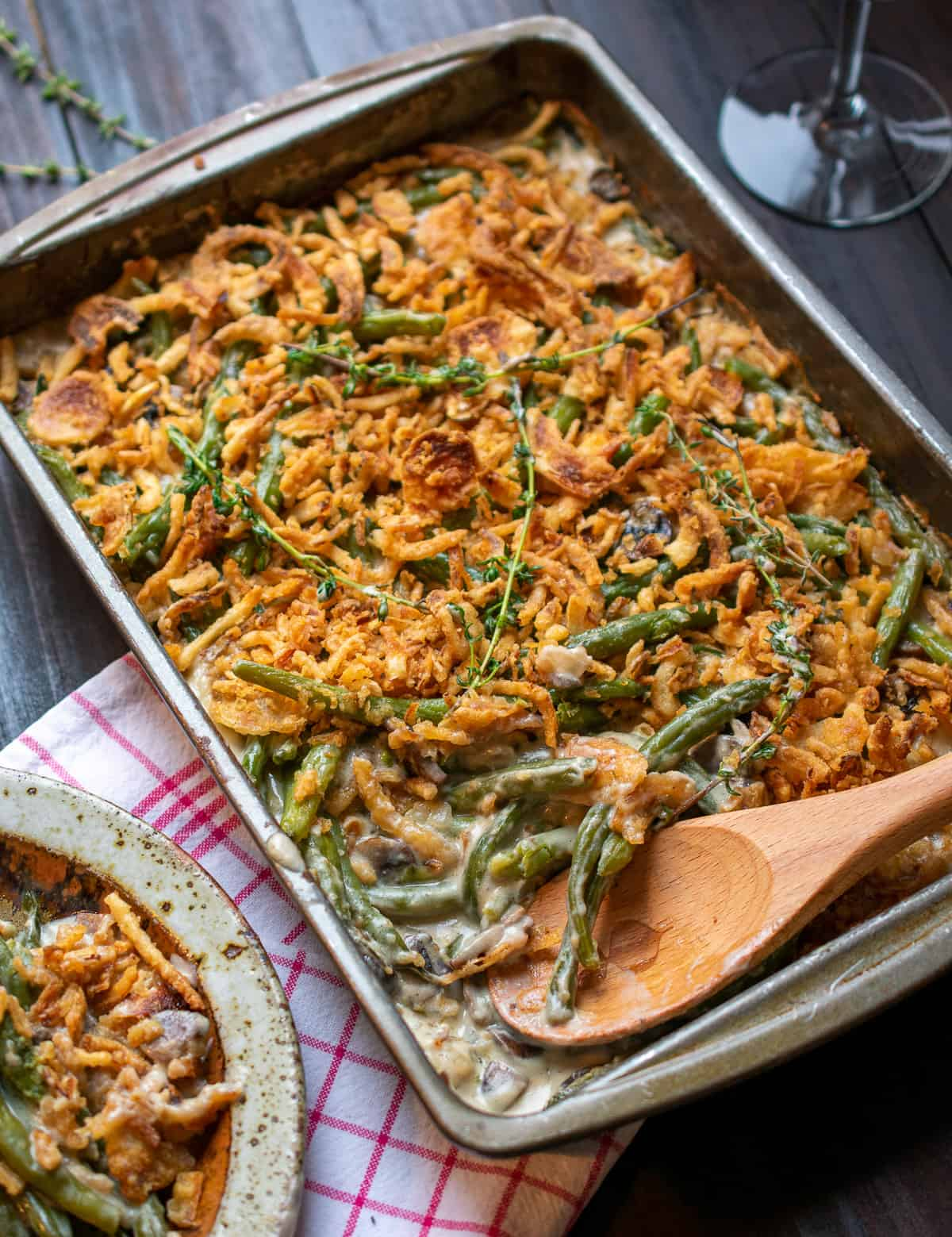 green bean casserole being spooned out to a dish