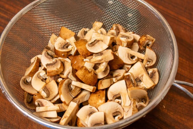 chopped mushrooms in a wire strainer