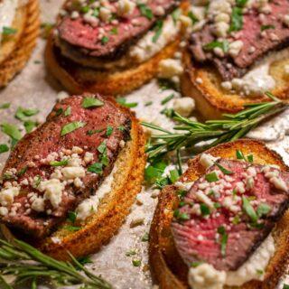 Beef tenderloin slices on toasted baguette