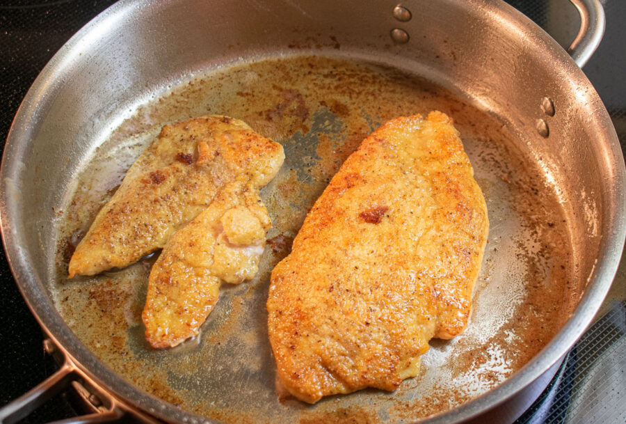 chicken cutlets browning in a skillet